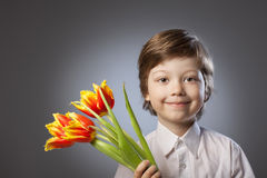 Kid with a bouquet of tulips Stock Photos