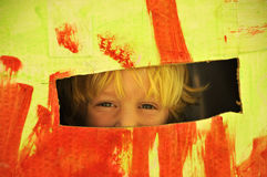 Kid in a Box. Kid Hiding in a Colorful Box Royalty Free Stock Photo