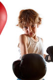 Kid boxing. Kid with attitude during boxing training with punching ball Royalty Free Stock Photography