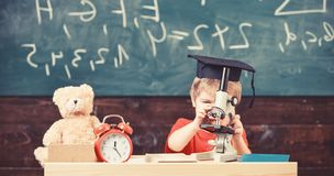 Kid boy in academic cap work with microscope in classroom, chalkboard on background. Child on busy face near microscope. Kid boy in academiap work with royalty free stock photos