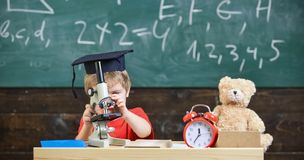 Kid boy in academic cap work with microscope in classroom, chalkboard on background. Child on busy face near microscope. Smart kid concept. First former stock image