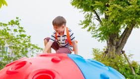 Kid boy and backpack having fun to play on children`s climbing toy at school playground,back to school outdoor activity.  stock photos
