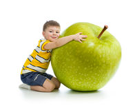 Kid boy with big green apple. Over white background Royalty Free Stock Image
