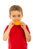 Kid boy biting slice orange Royalty Free Stock Photo