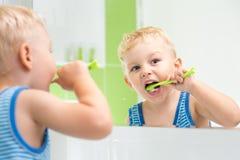 Kid boy brushing teeth. In bathroom royalty free stock photography