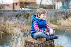 Kid boy with casual colorful clothes and eye wear glasses sitting on tree stump. Active blond kid boy with casual colorful clothes and eye wear glasses sitting royalty free stock images