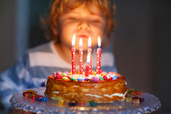 Kid boy celebrating his birthday and blowing candles on cake Stock Images