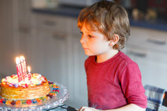 Kid boy celebrating his birthday and blowing candles on cake Royalty Free Stock Photo