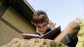 Kid reads a book sitting on a stone and scratching his head. Kid, boy, child reads a book sitting on a stone and scratching his head royalty free stock photo