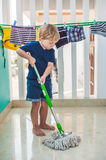 Kid boy cleaning room, washing floor with mop. Little home helper. Montessori concept Royalty Free Stock Photo