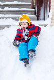 Kid boy in colorful clothes having fun with riding on snow, outd Royalty Free Stock Photo
