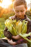 Kid boy with corn sitting on the grass in the garden. royalty free stock images