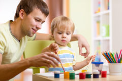 Kid boy and dad paint together. In nursery Stock Image