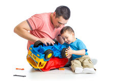 Kid boy and dad repair toy trunk. Kid boy and his dad repair toy trunk royalty free stock photography