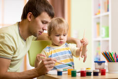 Kid boy and daddy paint together Stock Photo
