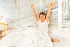 Kid boy doing his morning exercises sitting in bed Stock Photos