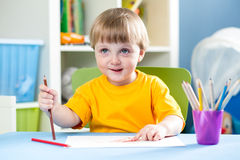 Kid boy draws with pencils indoors Stock Images