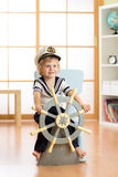 Kid boy dressed as a captain or sailor plays on chair like ship in his room. Child rotates the wooden steering wheel. Stock Photography