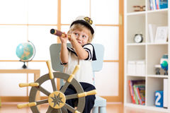 Kid boy dressed captain or sailor plays on chair as ship in his room. Child looks through telescope. Stock Photos