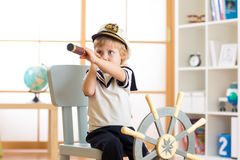 Kid boy dressed like a captain or sailor plays on chair as ship in his room. Child looks through telescope. Stock Image