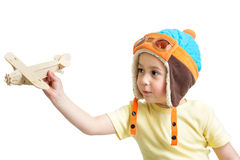 Kid boy dressed pilot and playing wooden air plane toy Royalty Free Stock Photo