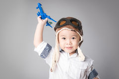 Kid boy dressed pilot and playing wooden air plane toy Stock Images