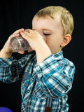 Kid boy drinking juice. Studio photo Stock Image