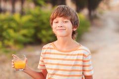 Kid boy drinking orange juice. Smiling young boy holding glass with orange juice outdoors at green background Stock Photo