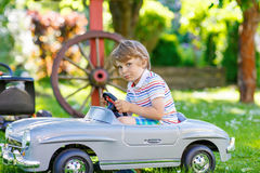 Kid boy driving with big toy car outdoors Royalty Free Stock Images