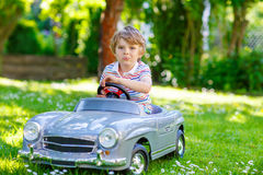 Kid boy driving with big toy car outdoors Royalty Free Stock Photography