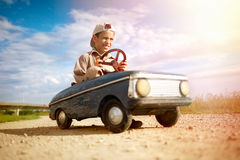 Kid boy driving big vintage toy car with a teddy bear. Young boy driving a vintage toy car, beautiful sunny day stock image