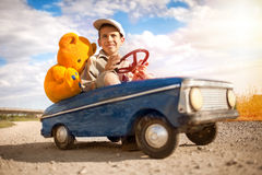 Kid boy driving big vintage toy car with a teddy bear Stock Images