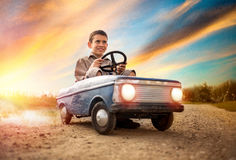 Kid boy driving big vintage toy car with a teddy bear Royalty Free Stock Photography