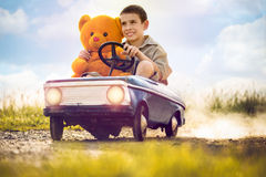 Kid boy driving big vintage toy car with a teddy bear Royalty Free Stock Photo