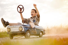 Kid boy driving big vintage toy car with a teddy bear. Young boy driving a vintage toy car, beautiful sunny day stock photos