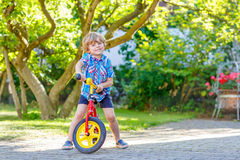 Kid boy driving tricycle or bicycle in garden Stock Photography