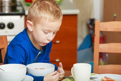 Kid boy eating breakfast, cereals and milk in bowl Royalty Free Stock Image