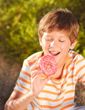 Kid boy eating donut outdoors. Teenager boy eating pink glazed donut outdoors Stock Image