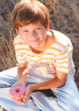 Kid boy eating donut outdoors. Young teenager boy eating tasty donut outdoors Stock Photography