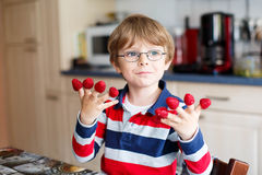 Kid boy eating fresh raspberries in kindergarten Stock Photos