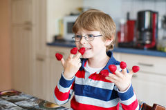Kid boy eating fresh raspberries in kindergarten Royalty Free Stock Image