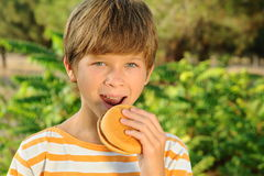 Kid boy eating hamburger outdoors. Young teenager boy eating tasty hamburger outdoors at green nature background Royalty Free Stock Photography