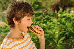 Kid boy eating hamburger outdoors Stock Photo