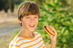 Kid boy eating hamburger outdoors. Young teenager boy eating tasty hamburger outdoors at green nature background Stock Photography