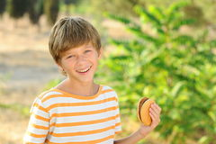 Kid boy eating hamburger outdoors. Young teenager boy eating tasty hamburger outdoors at green nature background Stock Images
