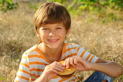 Kid boy eating hamburger outdoors. Young teenager boy eating tasty hamburger outdoors at green nature background Royalty Free Stock Image
