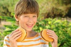 Kid boy eating hamburgers outdoors. Young teenager smiling boy holding two hamburgers outdoors Stock Images