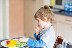 Kid boy eating healthy food in kindergarten or at home Royalty Free Stock Photography