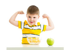 Kid boy eating healthy food and showing his strength Royalty Free Stock Image