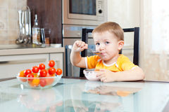 Kid boy eating at home in kitchen Stock Photo